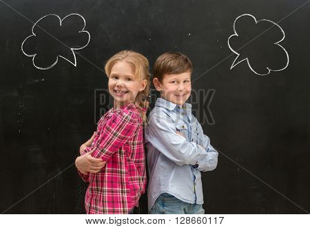 two little smiling children standing back to back with phrase clouds drawn on the blackboard