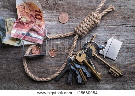 Hangman's Noose With House, Keys And Money On Brown Wooden Surface