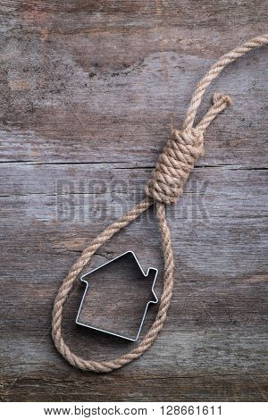 Small House Framed With Hangman's Noose On Brown Wooden Surface