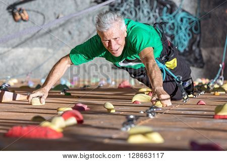 Portrait of Mature Male Climber Moving Up on Outdoor Climbing Wall Sporty Clothing on Fitness Training Intense but Positive Face Using Rope and Belaying Gear