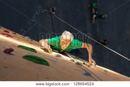 Elderly Male Climber Makes Hard Move on Outdoor Climbing Wall Sport Competitions Very Emotional Face Highlighted with Ray of Illumination