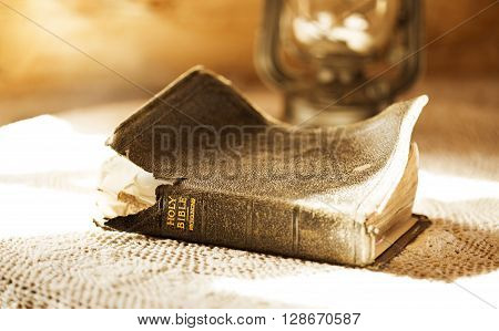 ancient and torn bible illuminated by a sunbeam