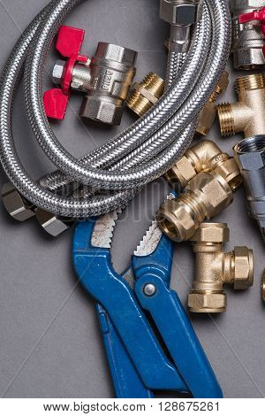 Adjustable Spanner With Assorted Plumbing Fittings And Hose On Grey