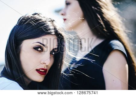 Sisters At Beach Hugging Each Other. Portrait Of Beautiful Young Girls, Sisters, Against The Backdro
