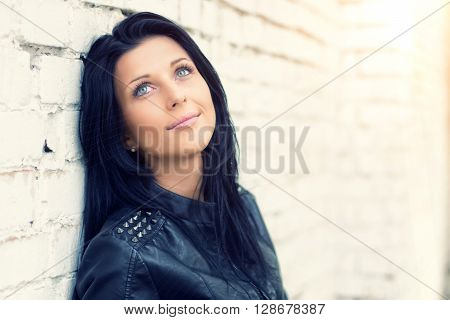 Beautiful brunette girl standing at white brick wall. She dreams, smiling, thinking about beauty. She is dressed in blue jeans and a black leather jacket. Look up