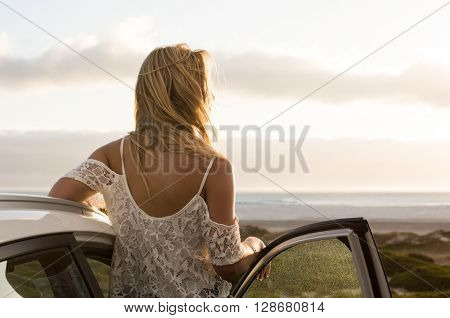 Young traveller woman enjoying sunset standing outside car. Serene woman leaning on car during sunset. Young woman on summer travel to the coast.