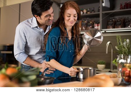 Couple cooking healthy food in modern kitchen. Man and woman at home preparing healthy food. Romantic young couple preparing dinner.