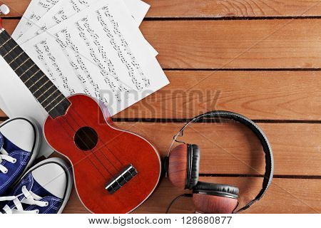 Small guitar, headphones, music sheet and gumshoes on wooden surface, top view