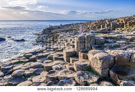Giants Causeway unique geological hexagonal formations of volcanic basalt rocks on Atlantic coast in County Antrim Northern Ireland in sunset light. UNESCO World Heritage Site