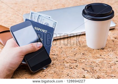 Cork table with closed laptop coffee cup and hand holding smartphone and american passport with dollars. Traveling concept
