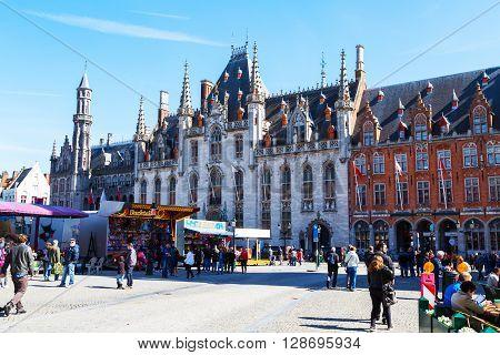 Bruges, Belgium - April 10, 2016: City Hall, Provinciaal Hof  neogothical building in Market square or Grote Markt, people walking