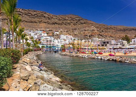 PUERTO DE MOGAN, GRAN CANARIA, SPAIN - APRIL 21, 2016: River at the beach area of Puerto de Mogan, a small fishing port on Gran Canaria, Spain. It's called a Little Venice of the Canaries.