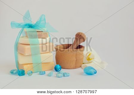 Spa setting in pastel and blue colors with different kind of natural soaps orchid and the wooden pounder on white background. Tower stack of different handmade soaps on white. Selective focus.