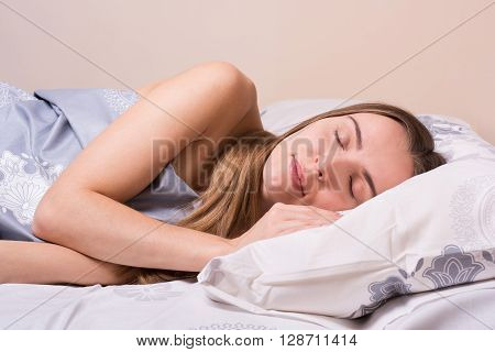 Beautiful young girl with long blond hair sleeping. Girl sleeps on a pillow, covered with a blanket. Having a good dream and smiling.