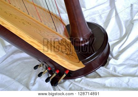 Closeup of the base of a dark wood concert grand pedal harp. Pedals and soundboard in detail.