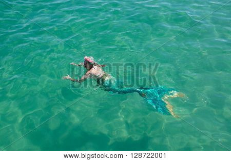 COOGEE,WA,AUSTRALIA-APRIL 3,2016: Live interactive mermaid entertainer swimming in the Indian Ocean at the Coogee Beach Festival in Coogee, Western Australia.