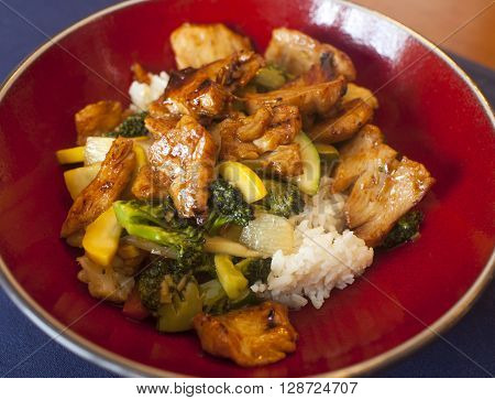 Chicken and vegetable stir fry up close on a red plate.