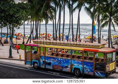 Honolulu, Hawaii, USA - Dec 15, 2015: Waikiki trolley shuttle bus parked along Kalakaua Avenue, near the Kuhio Beach Hula Mound, Waikiki Beach area. This is a cheap form of transport and is hugely popular among tourists.