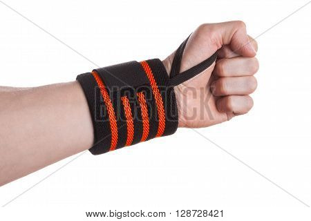 Clenched hand of a weightlifter with black and orange wrist support bandage isolated on white background