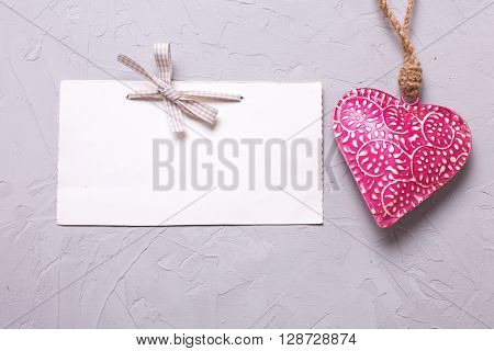 Pink decorative heart and empty tag on grey textured background. Selective focus. Place for text.