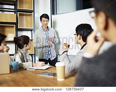 young asian businessman facilitating a group discussion or training in office.