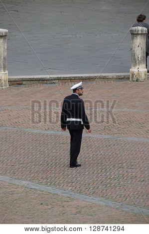 SIENA ITALY - CIRCA APRIL 2016: Italian Polizia Municipale (i.e. Town Police) officer patroling the main square aka il Campo