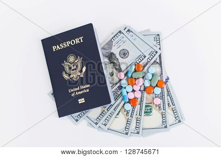 Top view of american passport dollars and pills on white surface. Concept of going abroad for medical treatment