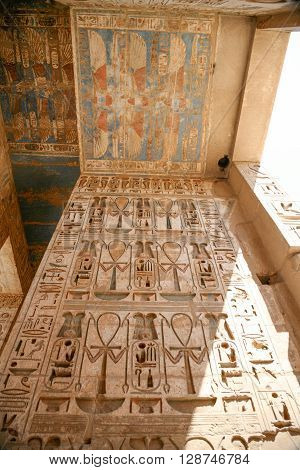 ceiling and wall of landmark Egyptian Temple of Ramses or Ramesses III at Medinet Habu monument with paintings carving figures and hieroglyphs in Luxor Egypt Africa