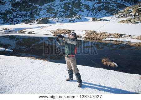 brunette woman with green red and brown clothes with camera as photographer taking selfie photo picture in winter snow Gredos mountain Avila Spain Europe