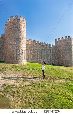 brunette tourist woman white shirt and brown trousers standing on the green grass with camera travel photo as photographer taking picture of medieval wall of Avila Spain Europe