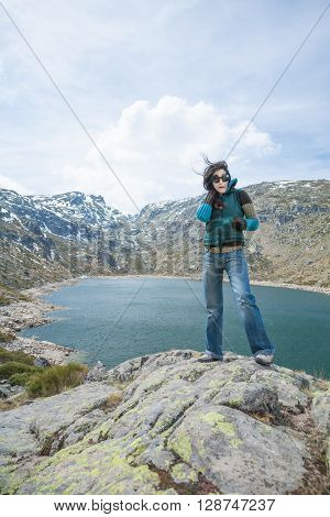 brunette woman with green winter vest blue jeans trousers  posing on top rock looking over lake valley in Gredos mountain Avila Spain