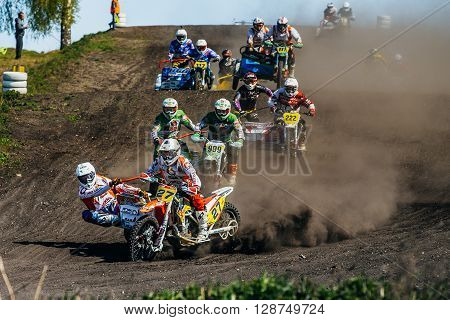 Miasskoe Russia - May 02 2016: group of motorcyclists with sidecars riding along a dusty track during Cup of Urals motocross
