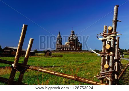 Kizhi Pogost on Kizhi Island, Karelia, Russia. Church of Transfiguration, Church of Intercession, and Bell-tower (UNESCO Cultural Heritage Site) seen from behind the Wooden Fence