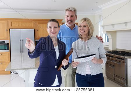 Female Realtor Showing Mature Couple Around House