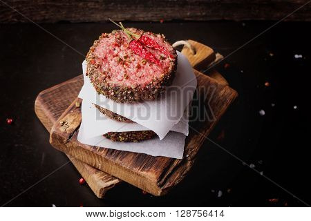Raw Ground beef meat Burger steak cutlets  with chili and seasoning on  rustic wooden board over dark marble background