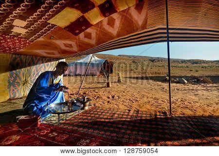 GUELMIMA, MOROCCO - OCTOBER 25, 2015:  Berber man preparing tea for guests at a camp near Guelmim in the Sahara desert , Morocco.