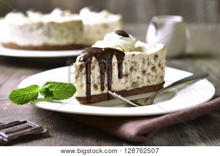 Cream mousse cake (no baked cheesecake) with bisquit crumbs on a white plate on rustic wooden background. poster