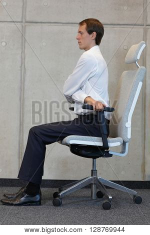 stretching with chair in office - business man exercising