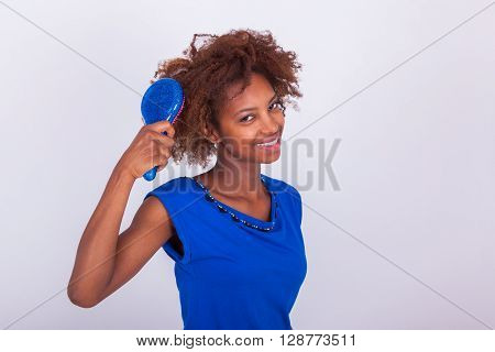 Young African American Woman Combing Her Frizzy Afro Hair - Black People