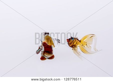 Bird and fish made of glass in hand on a white background