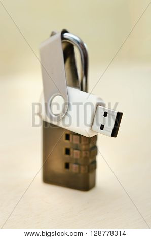 USB thumb drive with key locked on wooden background