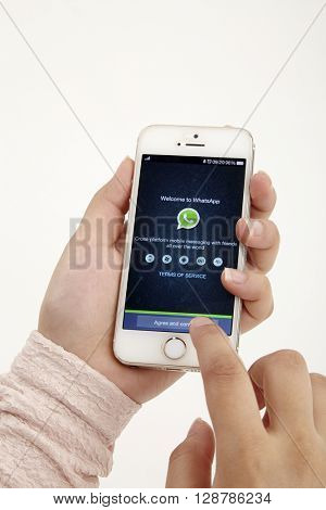 KUALA LUMPUR, MALAYSIA - 8th Augst 2015, Woman try to use social Internet service WhatsApp screen on white background.