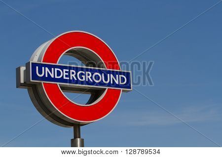 LONDON, UK - MAY 5, 2016. A London Underground sign against a clear, blue sky, marking the entrance to an underground train station.