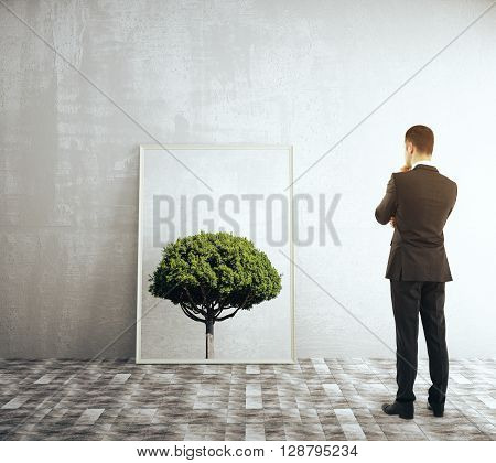 Businessman looking at a framed picture of a tree in room with concrete wall and tile floor. 3D Rendering