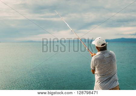 PEFKOHORI GREECE - MAY 26 2015: Man wearing a cap is back and fishing in the Aegean sea