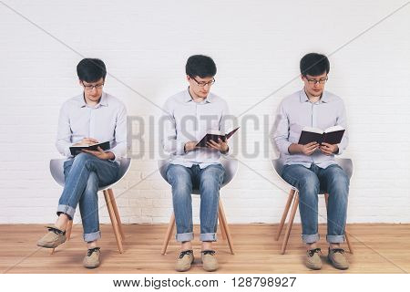 Brick interior with three different photos of one man organized into one picture collage. In one of the pictures the man is writing in a notepad and reading a book in the rest