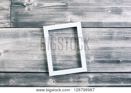 See through picture frame hanging on wooden wall. Mock up