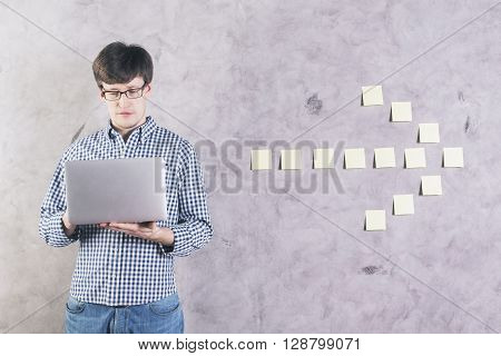 Concentrated caucasian man using laptop next to sticker arrow glued onto concrete wall