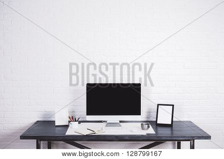 Designer desktop with blank computer screen picture frames and other items on white brick background. Mock up