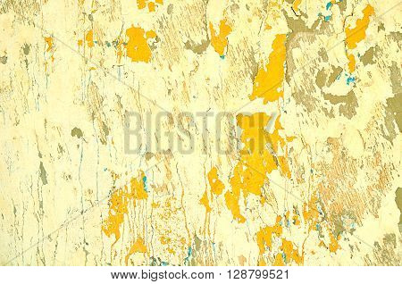 Textured vintage background - peeling light yellow stucco and chipped orange paint with blue streaks on the old wall surface. Architecture texture vintage background.